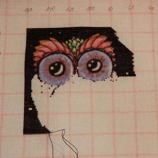In progress cross-stitch project showing an owl with just the head stitched out.