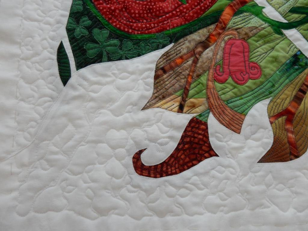 Lower left corner of quilt, showing the white-on-white quilting of a rose hedge in the foreground.