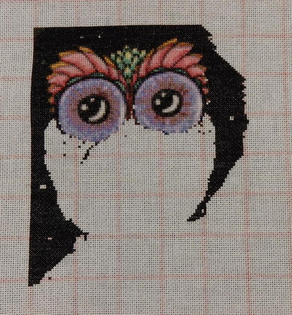 In-progress picture of a cross stitch showing a colourful owl.