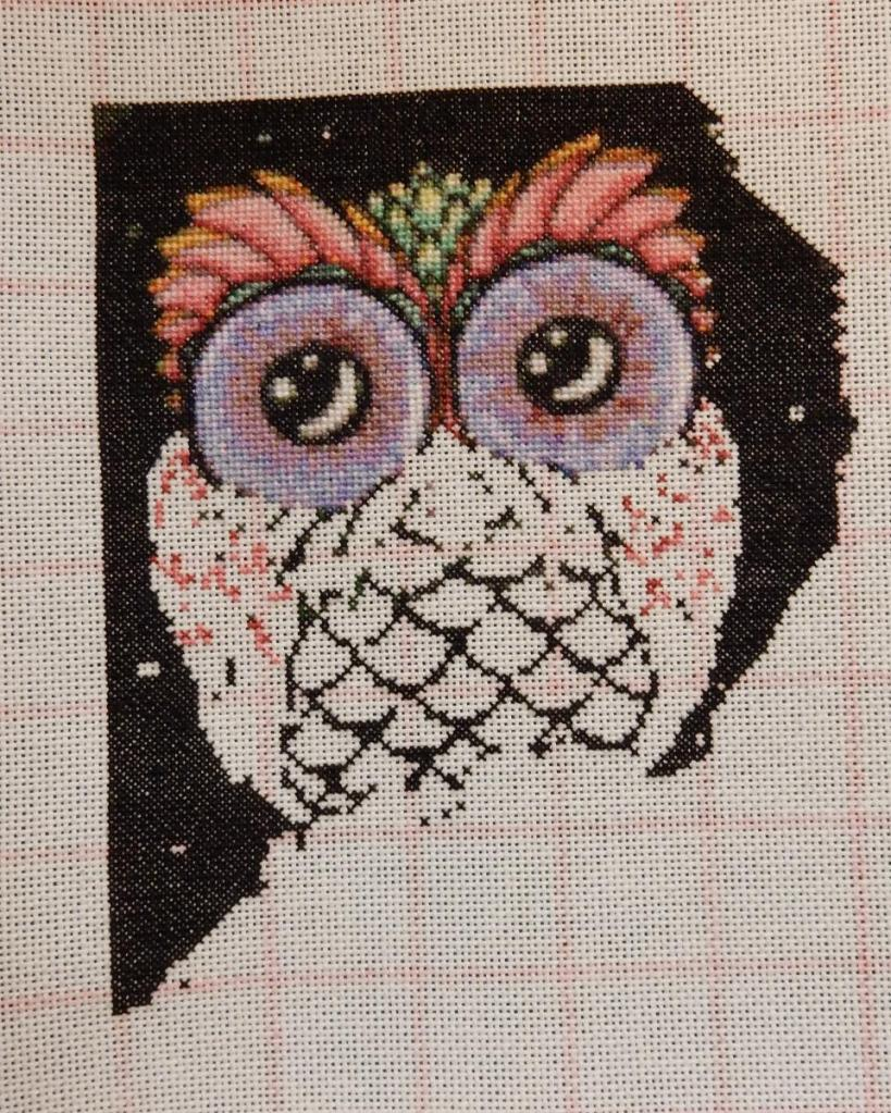 Progress shot of counted cross-stitch embroidery of a cute owl