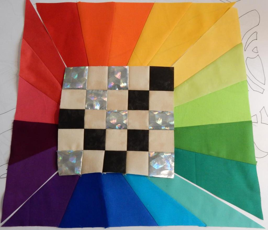checkerboard 5-patch with light and dark/silver squares, surrounded by a rainbow colourwheel radiating out.