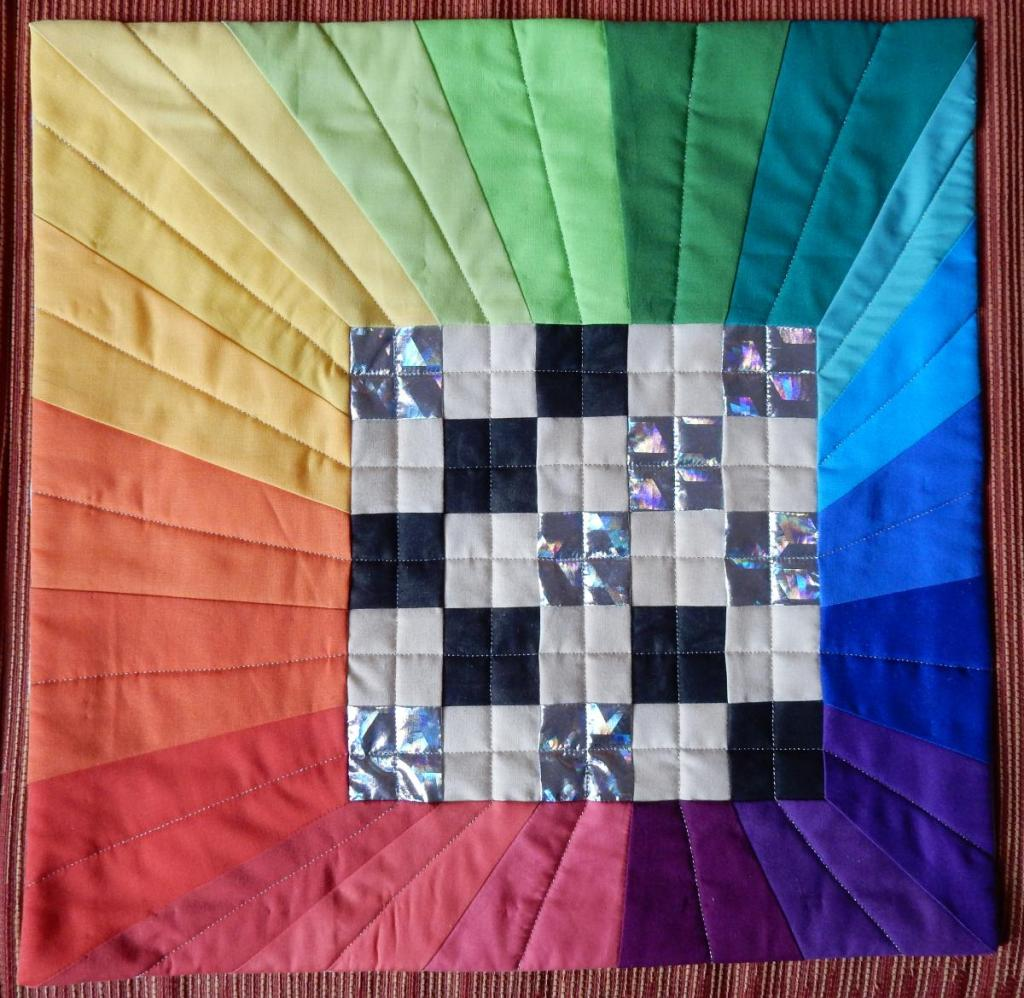 Finished 2020 Challenge quilt - silver/black and white checkerboard 5-patch with asymmetric rainbow colourwheel surrounding it.