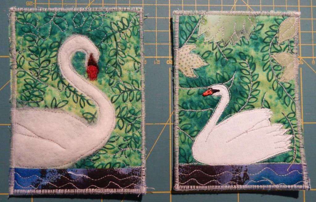 Two fabric postcards each with a swan on water. On the left, a needle-felted swan, on the right, an appliquéd one.