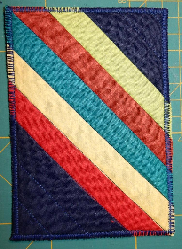 Textile postcard with five diagonal stripes on a dark blue background.