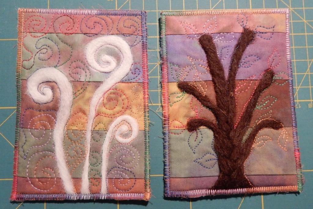 Two textile postcards with needle-felting on top of a striped background from hand-dyed fabric. Three spirals in white on the left and a stylized tree on the right.
