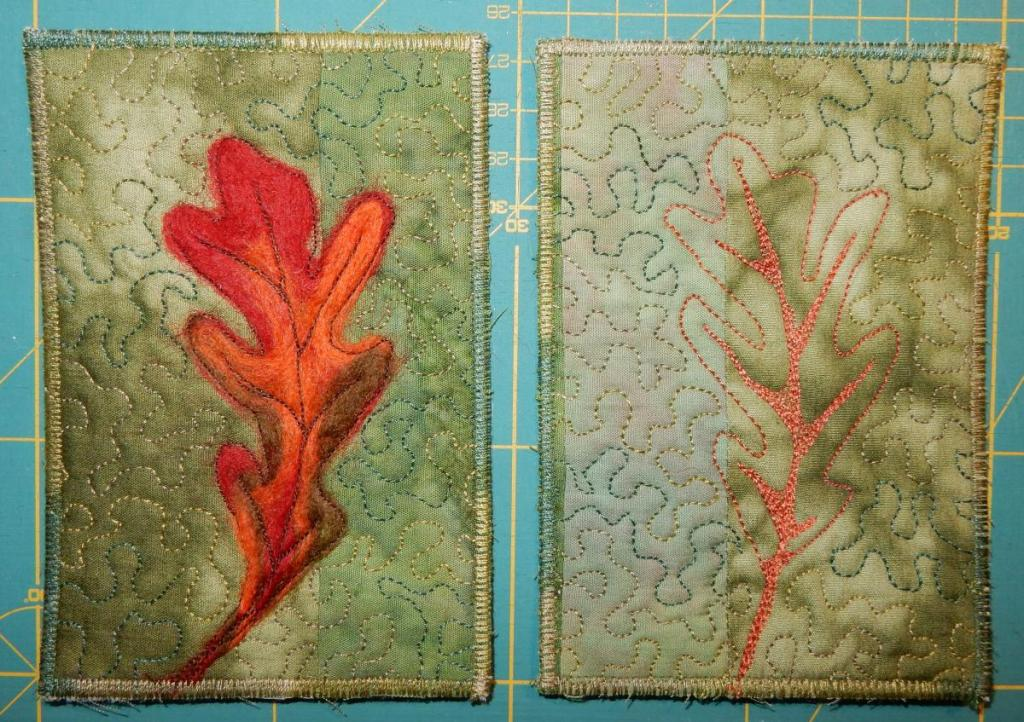 Two fabric postcards with an olive green backgrounds and a single oak leaf on top - on the left needlefelted in red, orange and brown, on the right just outlines machine-quilted.
