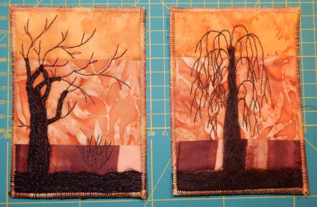 Two textile postcards showing dark trees against a brown and golden background.