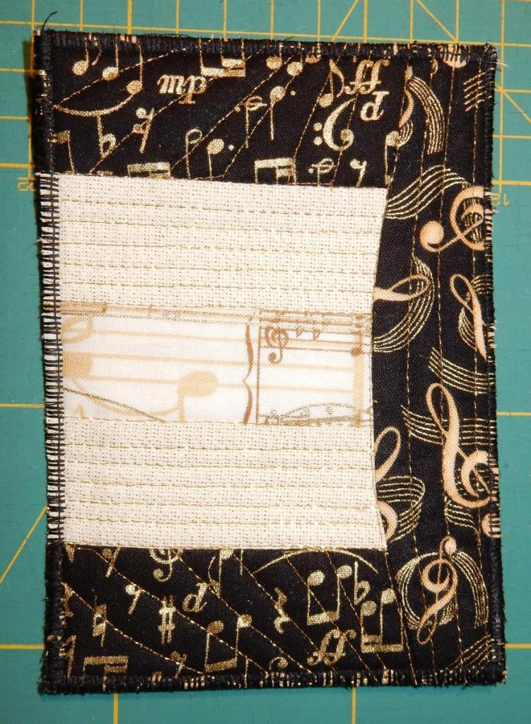 Textile postcard in beige and black fabrics showing musical symbols, mostly in gold.
