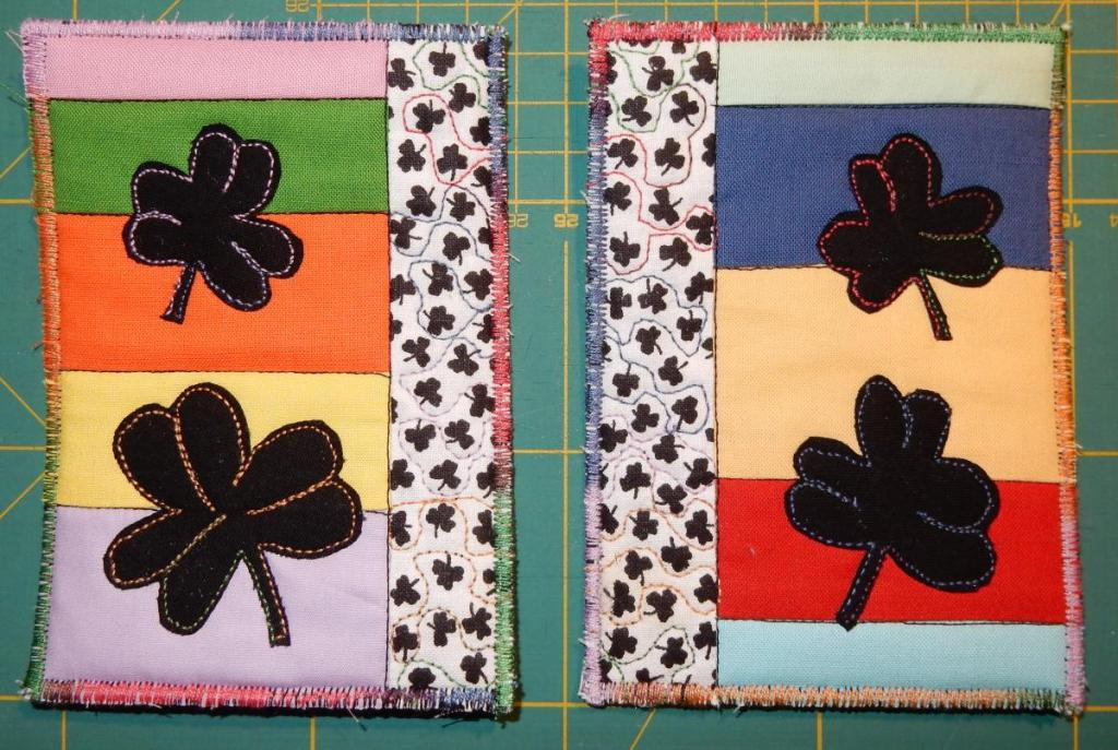 Pair of textile cards with a vertical strip of white fabric with tiny black cloverleaves on it. Rest of the card are horizontal stripes in mostly pastel solids, overlaid with big black appliquéd cloverleaves.