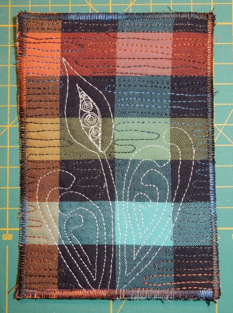 Textile postcard from a dark checkered fabric with a white abstract flower and leaves quilted on top.