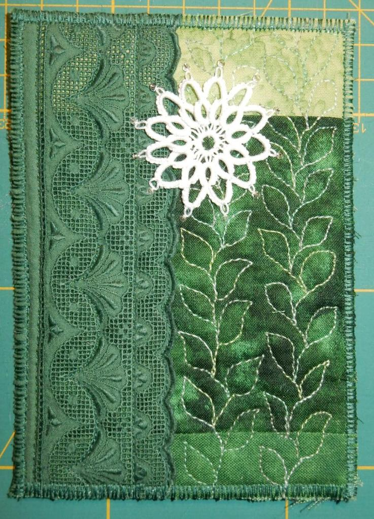 Textile card with a green background. Vertical strip of green machine lace on the left, white tatted flower with added beads.