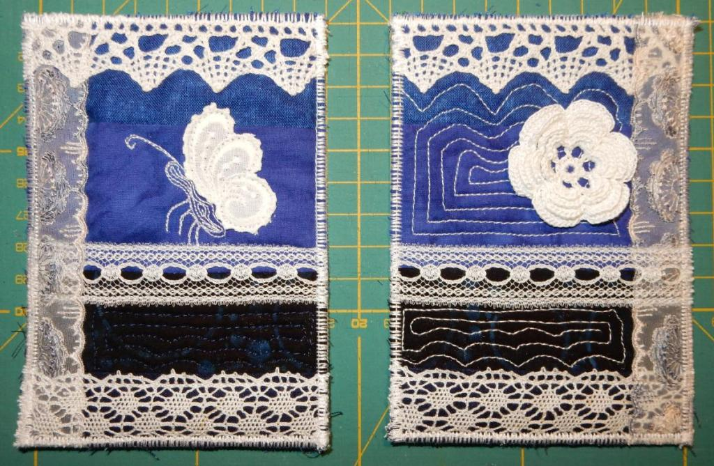 Two textile postcards with a blue background, overlaid with strips of lace. Focal point on the left card is a butterfly from machine-stitched lace, and the right a dimensional flower in Irish crochet lace.