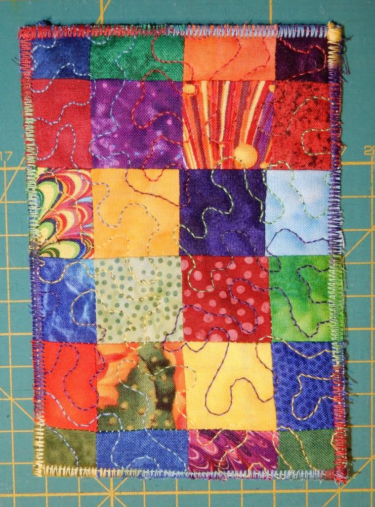 Textile postcard consisting of small squares of colourful fabric randomly assembled.