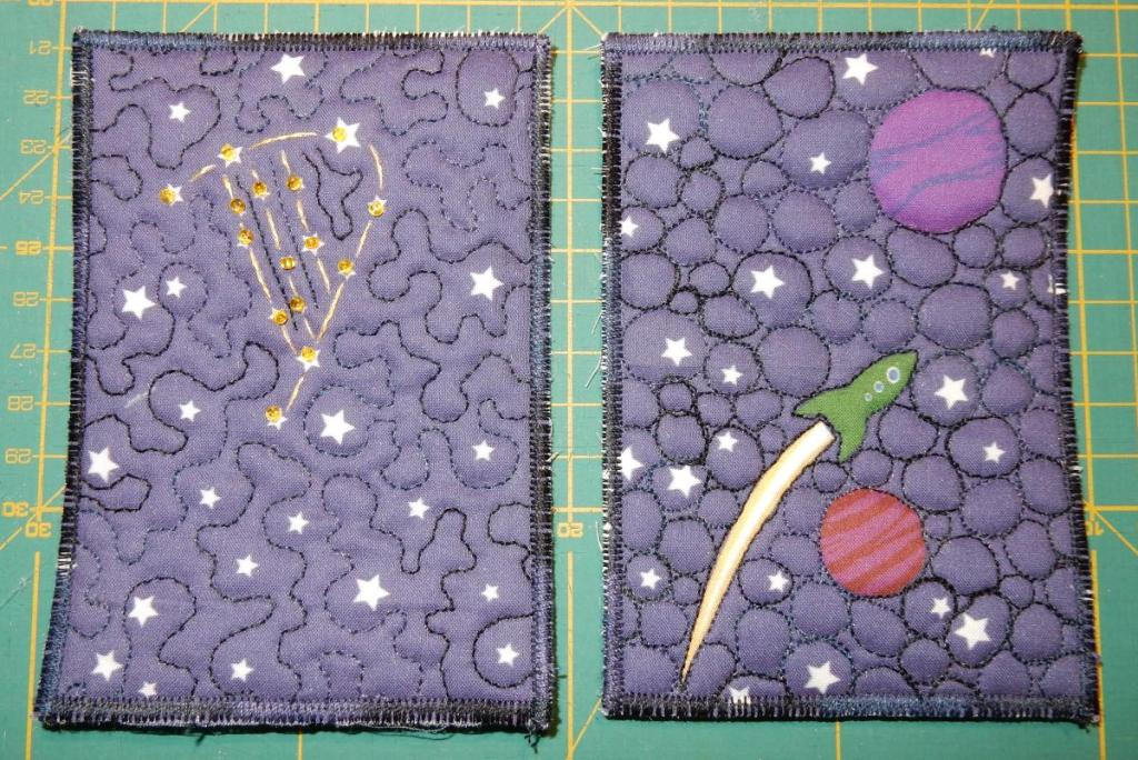 "Two textile postcards from a printed fabric sample with a dark blue/violet background. Left one has the letter ""D"" from the Dublin 2019 Logo as a star constellation, right one has two planets and a rocket."