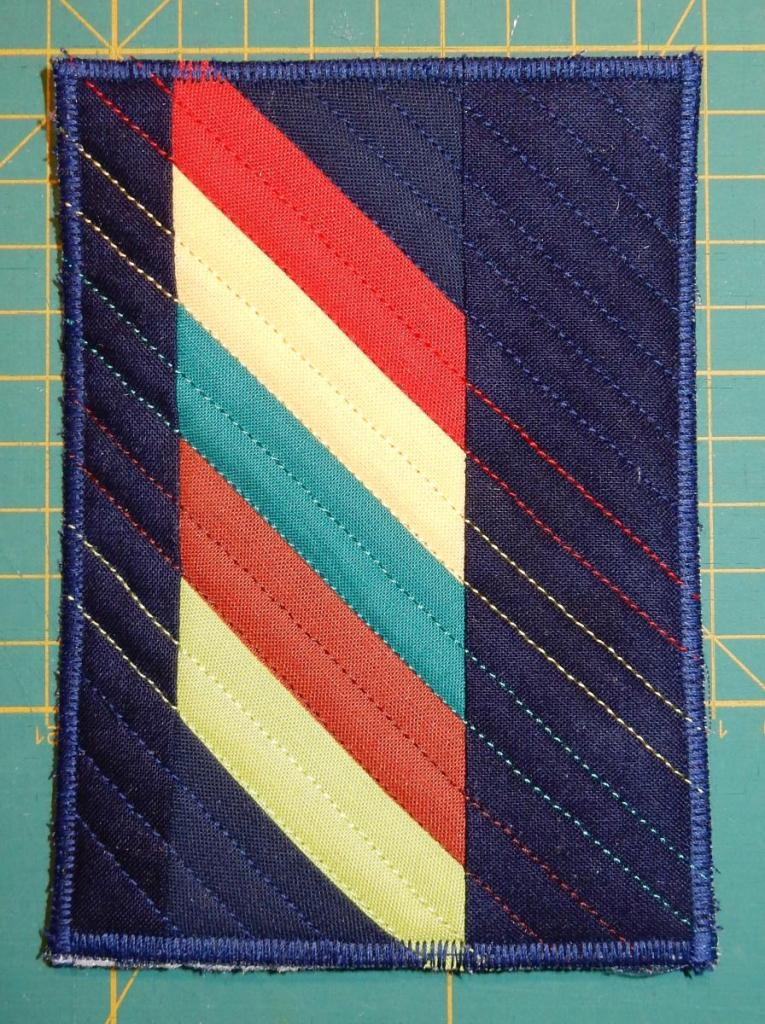 Textile postcard with colourful diagonal stripes on a dark blue background.