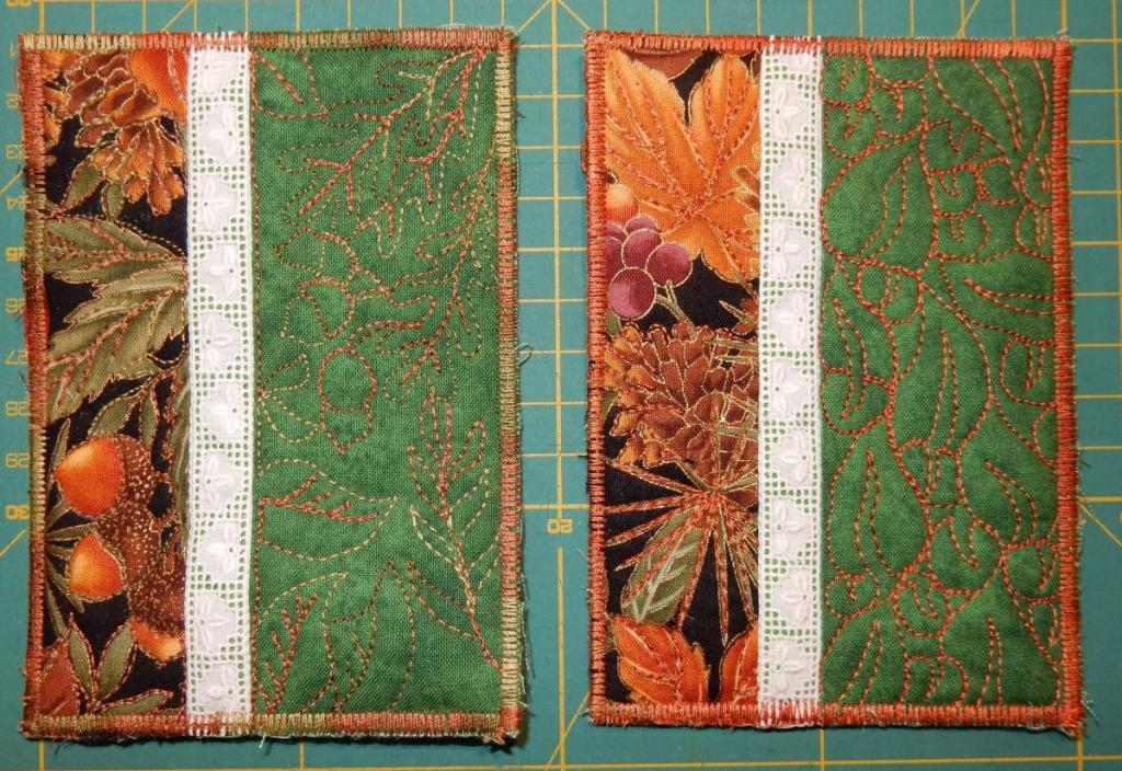 Two textile postcards with a fall theme - print with leaves and cones and berries on a black background, narrow lace edging, quilted leaves on green background.