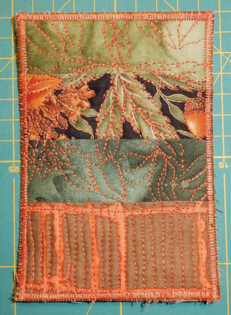 Textile postcard in greens and oranges with a stripe of autumn-themed printed fabric as focal point.
