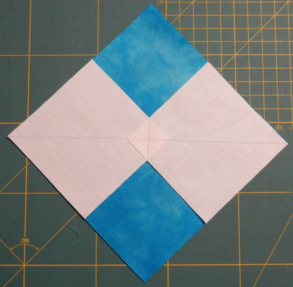 Blue square of fabric on the diagonal, with two smaller white squares on top in the left and right corners, overlapping in the middle.