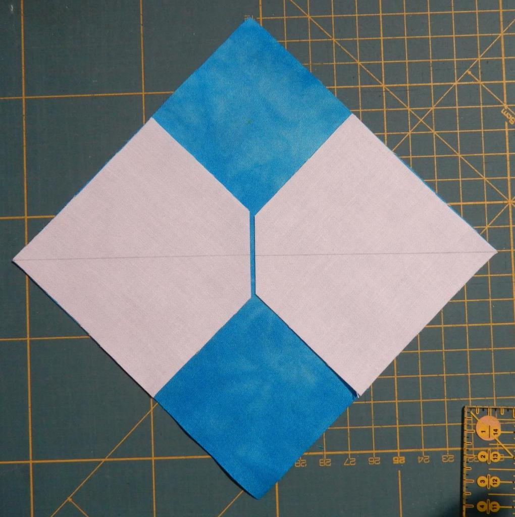 Square piece of blue fabric on the diagonal with two smaller white squares on top - overlapping fabric cut away where the white squares meet.