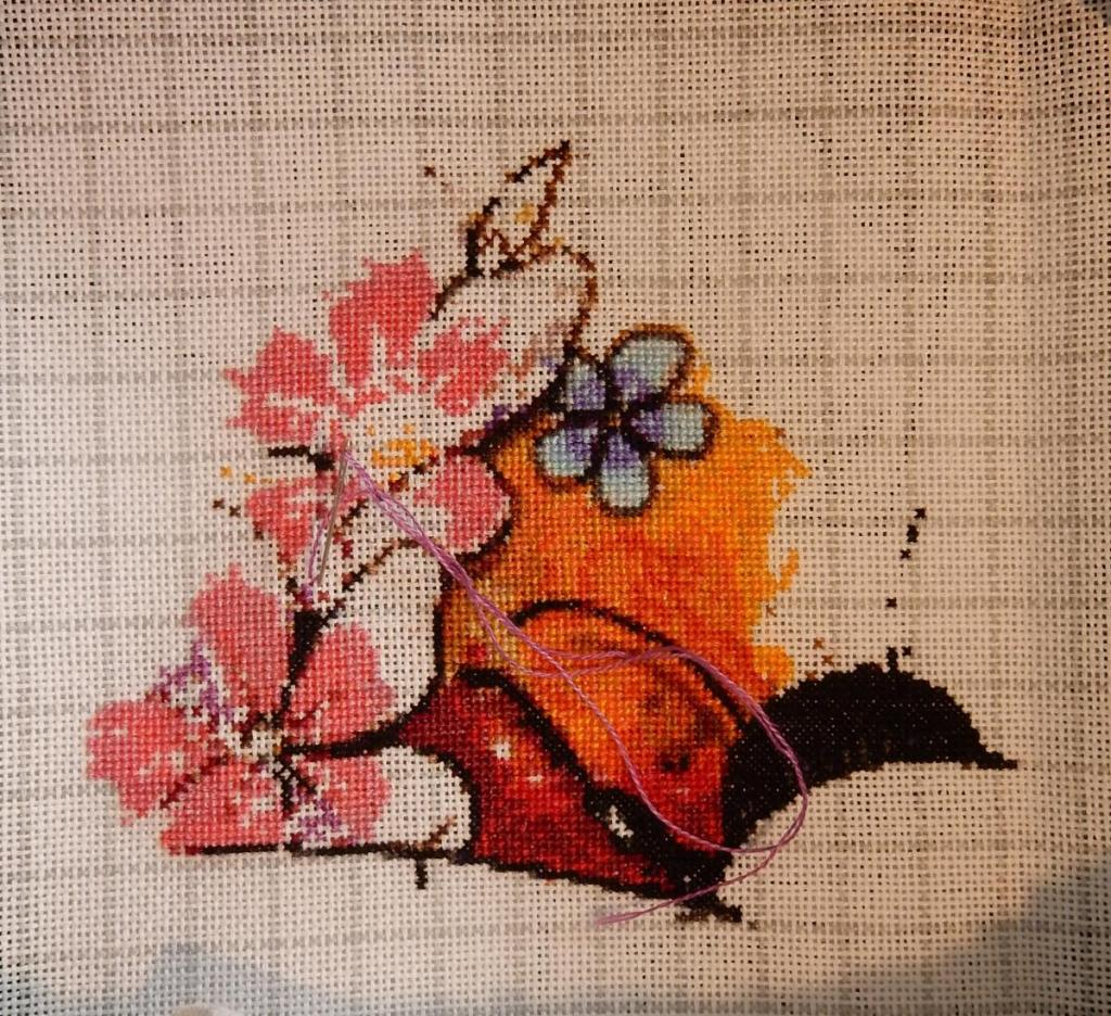 Progress picture of cross-stitch image showing the head of a bee, some red-orange background and a couple of partially done pink flowers on the left.