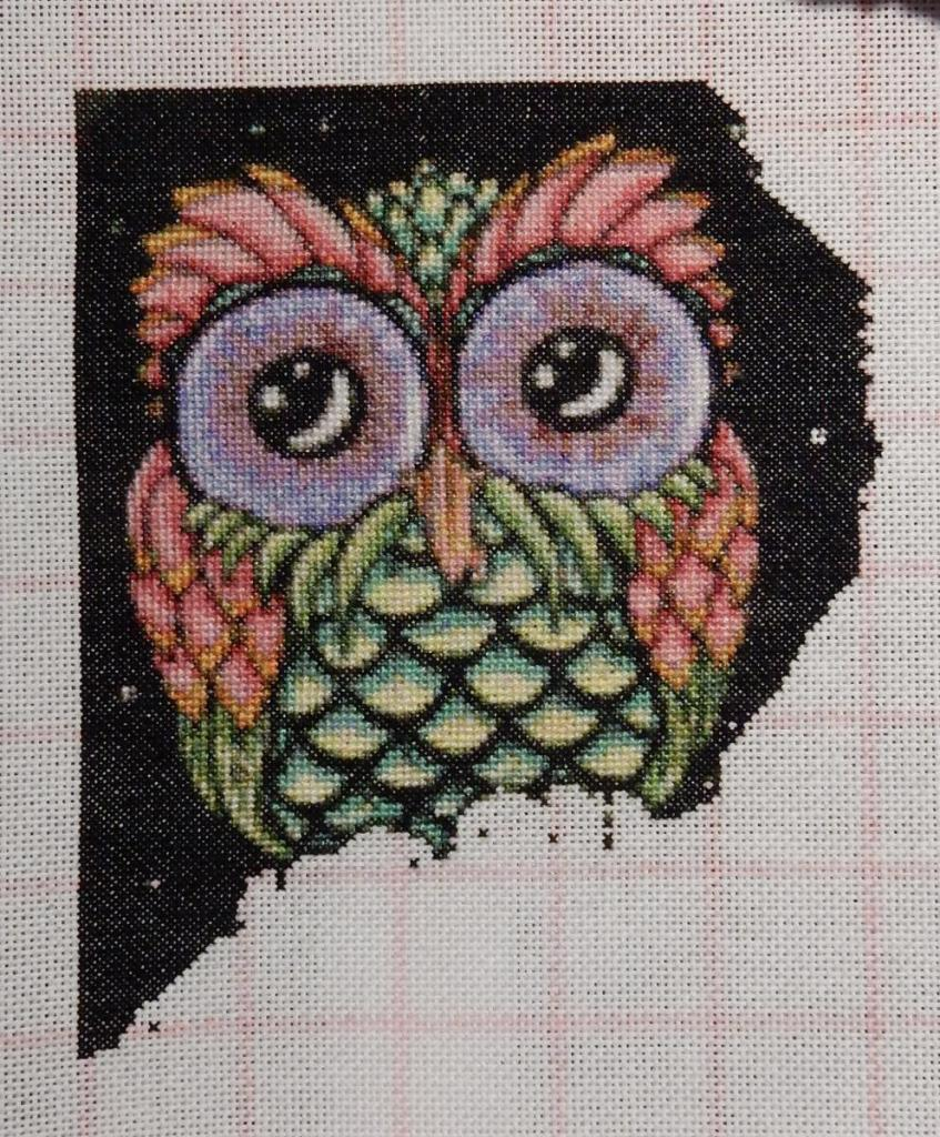 Cross-stitched wol in reds and green with finished head and body.