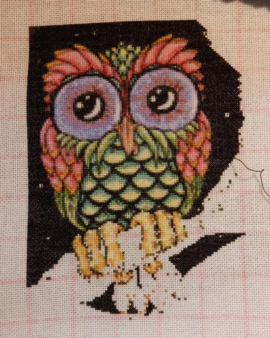 In progress picture of a colourful owl in counted cross-stitch
