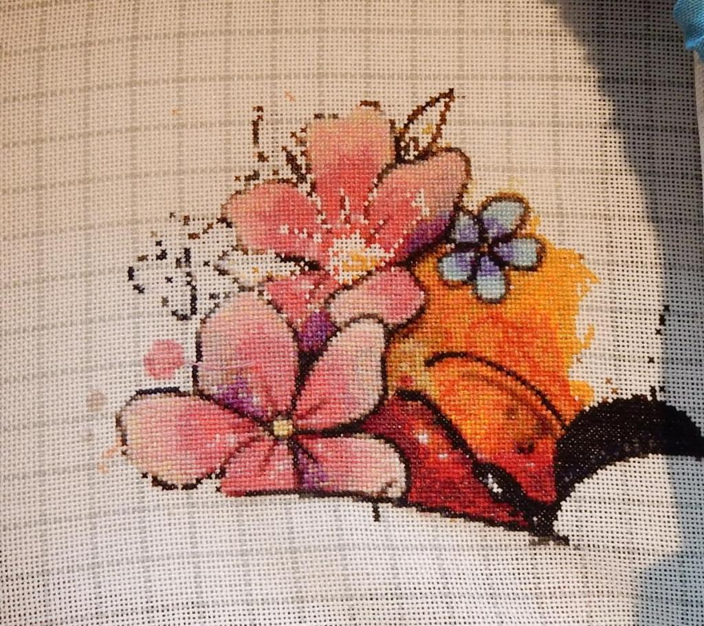 In-progress shot of a counted cross-stitch project, featuring two big pink flowers on top of each other.