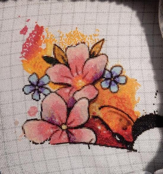 In-progress shot of a counted cross-stitch project, featuring two big pink flowers on a orange and red background.