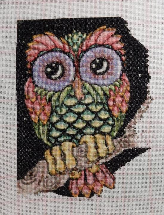 Progress picture of a cross-stitched owl sitting on a branch.