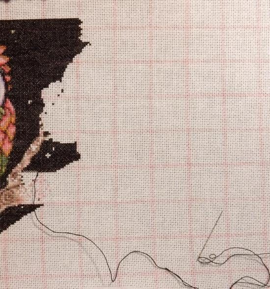 counted cross-stitch project in progress - black background on the left side of empty fabric showing the outline of the next coloured section.
