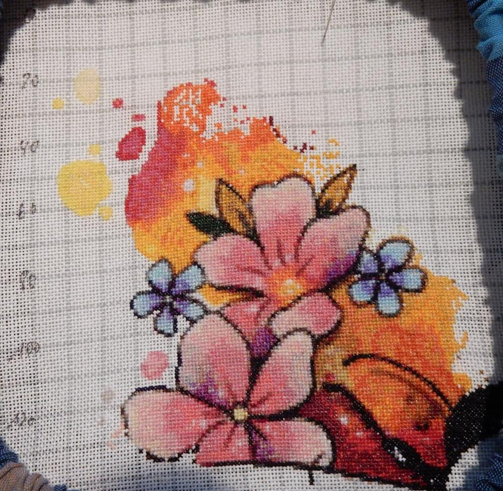 In progress picture of a colourful cross-stitch-project of a bee featuring the red-orange-yellow background on the opper left of the image.