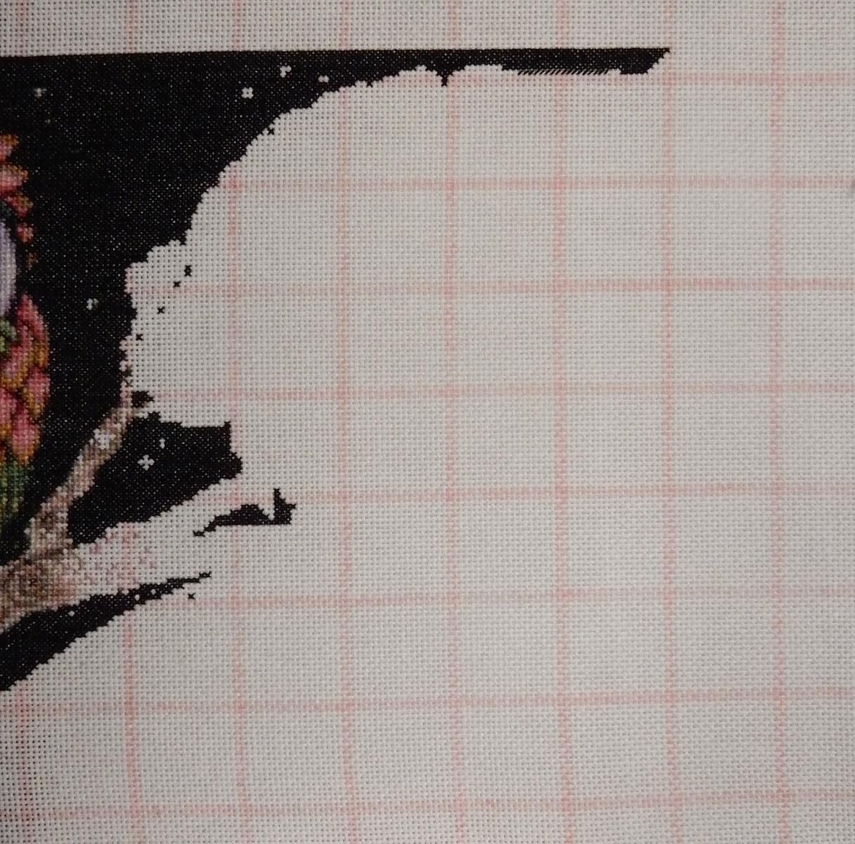 In progress picture of a counted cross-stitch pattern, visible is the negative space in the black background on top of the second owl.