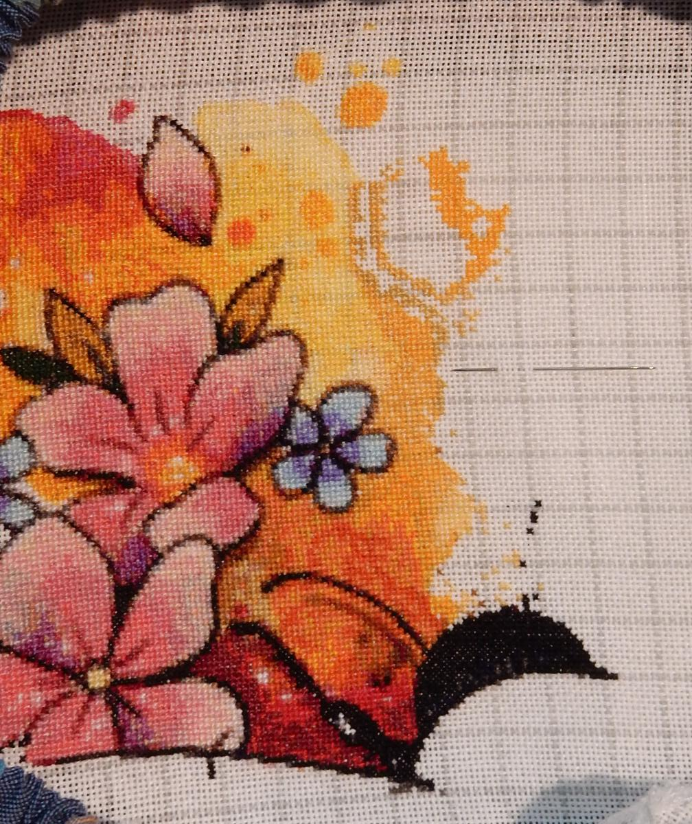 In-progress shot of a cross-stitch pattern, showing a couple of pink flowers on the lower left on top of a yellow-orange background. In the unfinished part to the right a hexagonal honeycomb form is appearing.