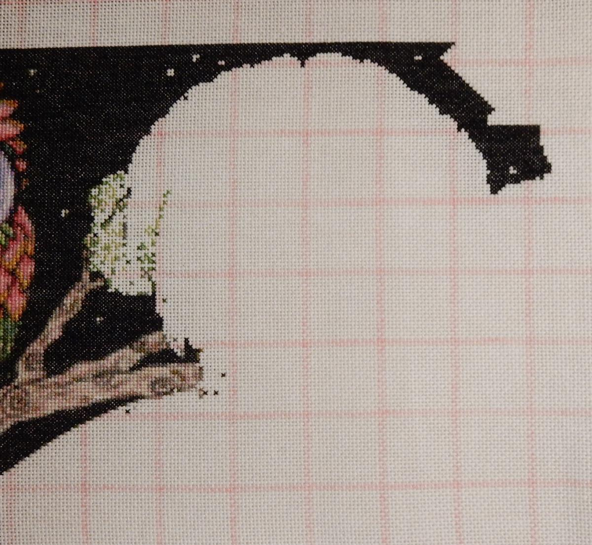 In-progress shot of a counted cross-stitch-project. The black background at the top is outlining the shape of the head of an owl. To the left, there are some finished branches and the start of an area of green foliage.