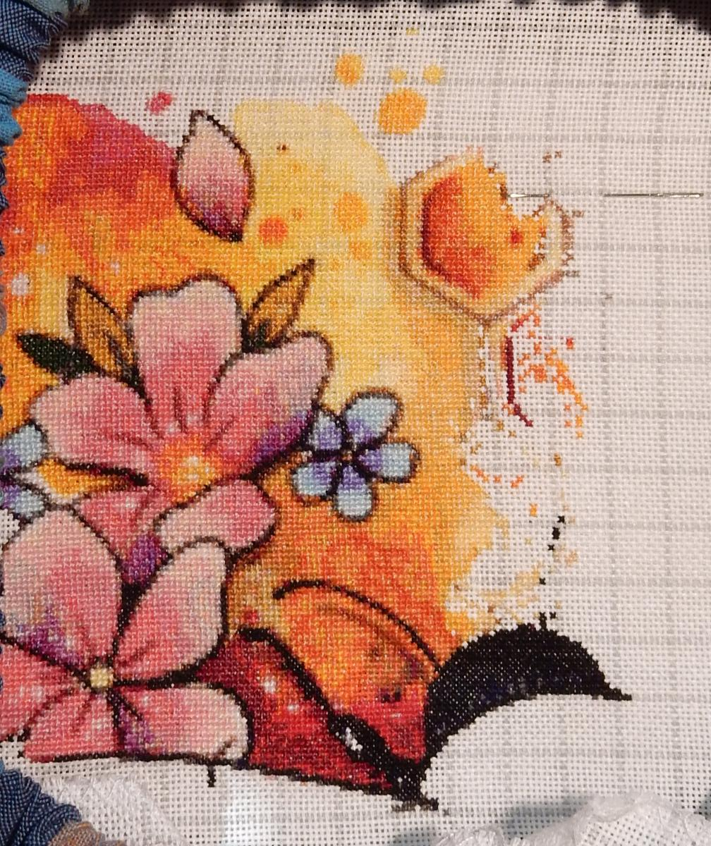 In progress-shot of a counted cross-stitch project with a yellow-orange-red background. On the left, some big pink and small blue flowers, on the upper right, a hexagon from a honeycomb.